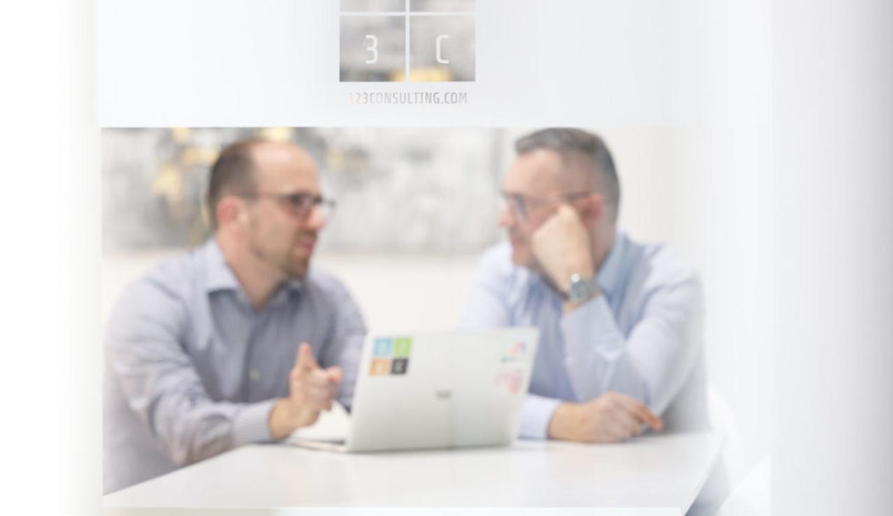 Logo der 123Consulting auf einer Milchglasscheibe mit Harald Grabner und Thomas Apollonio dahinter neben einem Notebook im Gespräch.