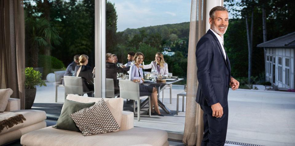 Klassenlotterie Gewinner Mann in Anzug vor verglaster Terasse auf der Menschen Abendessen 123C Partner Hohe Brücke