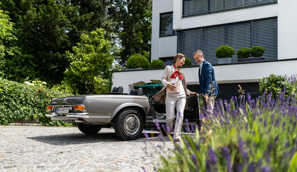 Lottogewinn Mann öffnet Cabriotür für Frau Einfahrt vor großem weißem Haus 123Consulting Partner Hohe Brücke